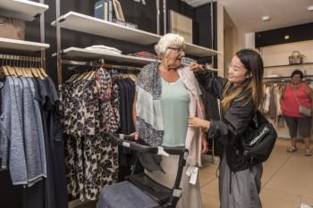 Femme à la recherche de nouveaux vêtements en marchant avec son rollator Rollz Flex